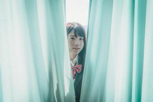 カーテンから顔を出す女子高生の写真素材 [FYI01199606]