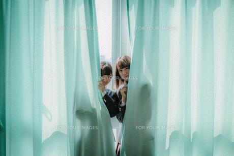 カーテンから顔を出す女子高生2人の写真素材 [FYI01199613]