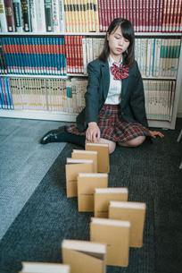 図書室で本を使ってドミノ倒しをしている女子学生11の写真素材 [FYI01199634]