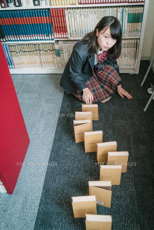図書室で本を使ってドミノ倒しをしている女子学生10の写真素材 [FYI01199635]