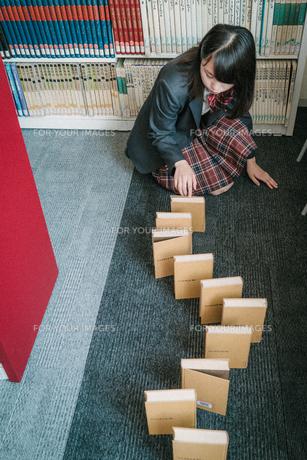 図書室で本を使ってドミノ倒しをしている女子学生9の写真素材 [FYI01199636]