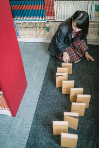図書室で本を使ってドミノ倒しをしている女子学生8の写真素材 [FYI01199637]
