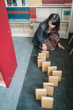 図書室で本を使ってドミノ倒しをしている女子学生6の写真素材 [FYI01199638]
