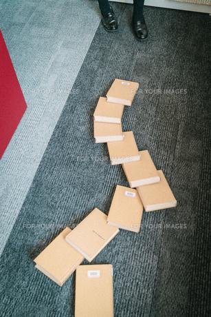 図書室で本を使ってドミノ倒しをしている女子学生7の写真素材 [FYI01199639]