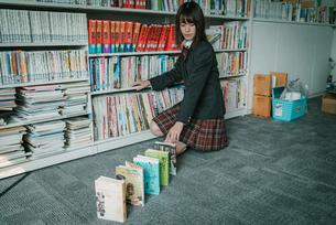 図書室で本を使ってドミノ倒しをしている女子学生5の写真素材 [FYI01199640]