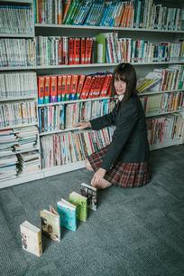 図書室で本を使ってドミノ倒しをしている女子学生3の写真素材 [FYI01199642]