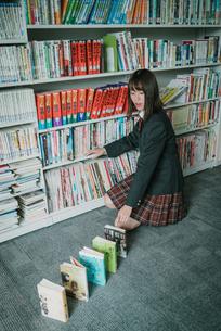 図書室で本を使ってドミノ倒しをしている女子学生2の写真素材 [FYI01199643]