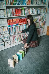 図書室で本を使ってドミノ倒しをしている女子学生の写真素材 [FYI01199644]