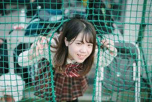 ソフトボール用ネットから顔を出す女子高生3の写真素材 [FYI01199652]