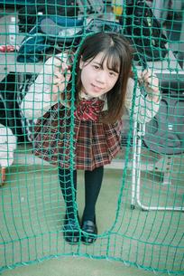 ソフトボール用ネットから顔を出す女子高生の写真素材 [FYI01199654]