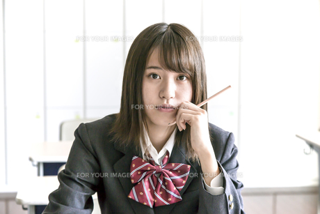 教室で鉛筆を持ちカメラ目線の女子高生の写真素材 [FYI01199848]