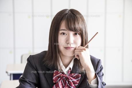 教室で鉛筆を持ち見つめる女子高生のアップの写真素材 [FYI01199849]