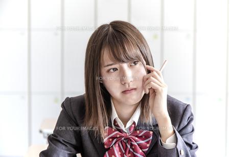 教室で鉛筆を持ち考える女子高生のアップの写真素材 [FYI01199852]