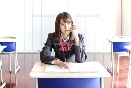教室で鉛筆を持ち考える女子高生の写真素材 [FYI01199855]