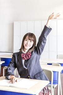 教室で手を上げる笑顔の女子高生の写真素材 [FYI01199857]