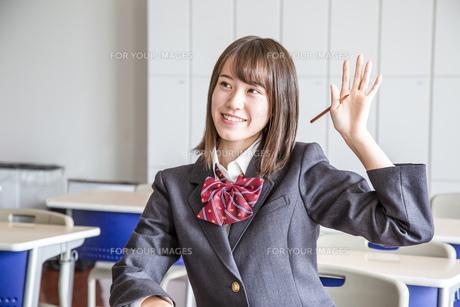 教室で手を上げる笑顔の女子高生の写真素材 [FYI01199860]