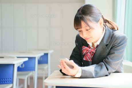 教室でスマホを見る女子校生の写真素材 [FYI01199911]