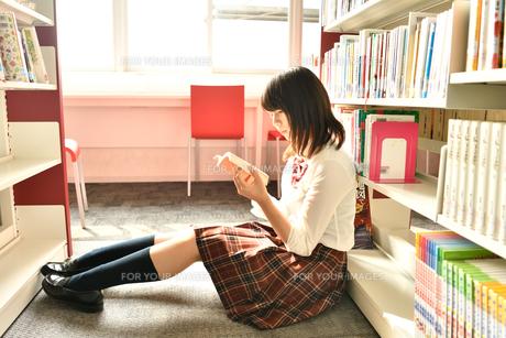 図書室で読書する女子校生の写真素材 [FYI01199943]