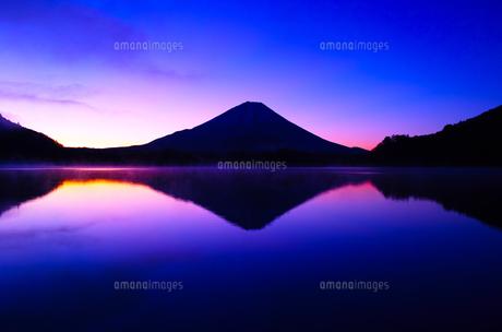 夜明け前の毛嵐が立ち込める精進湖と富士山の写真素材 [FYI01199952]