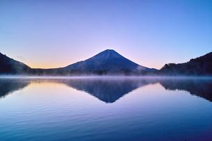 夜明け前の毛嵐が立ち込める精進湖と富士山の写真素材 [FYI01199954]