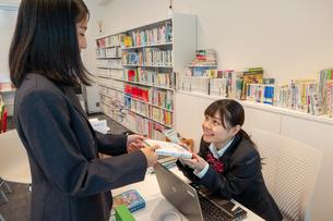 図書室で本を借りる女子高校生の写真素材 [FYI01199982]