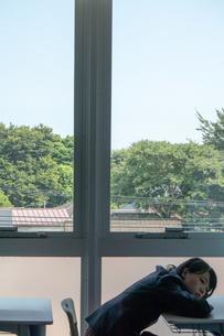 窓際でうつ伏せになり物思いに耽る女子高校生の写真素材 [FYI01199985]