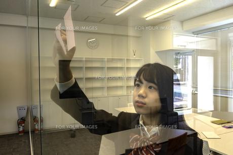ガラスに付箋を貼る女子高校生の写真素材 [FYI01199988]