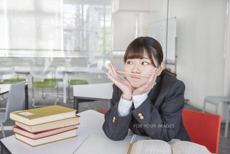 図書室で鉛筆を鼻にハサミ勉強する女子高生の写真素材 [FYI01200010]