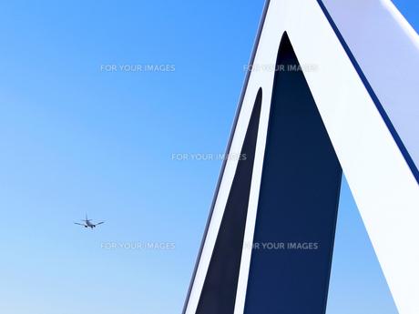トラス橋の彼方にジェット機が飛ぶ風景の写真素材 [FYI01200301]