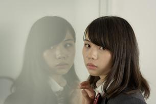ガラスに映る女子高生の写真素材 [FYI01200393]