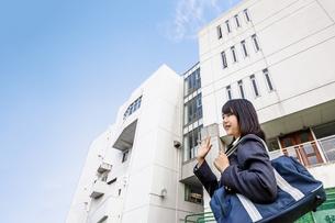青空と校舎をバックに友に手を振る女子高生の下校イメージの写真素材 [FYI01200533]