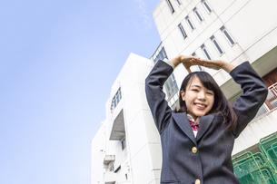 青空と校舎をバックに手でOKをする女子高生の写真素材 [FYI01200536]