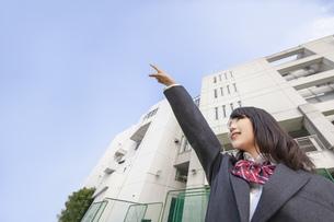 青空と校舎をバックに左上を指差しをする女子高生の写真素材 [FYI01200538]