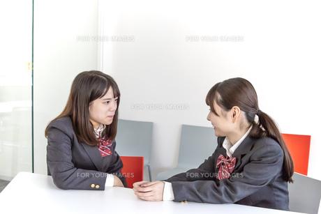 同級生と向かい合って話をする女子高生イメージの写真素材 [FYI01200659]