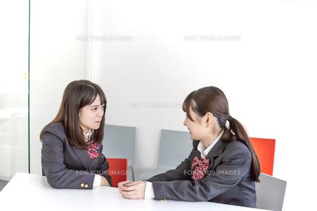 同級生と向かい合って話をする女子高生イメージの写真素材 [FYI01200660]