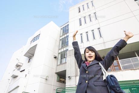 青空と校舎をバックにバンザイをする女子高生の写真素材 [FYI01200661]