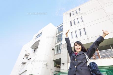 青空と校舎をバックにバンザイをする女子高生の写真素材 [FYI01200662]