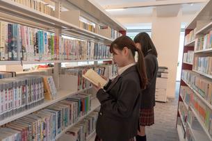 図書室で本を探す二人の女子高校生の写真素材 [FYI01201053]