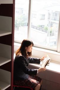 夕方に窓際で本を読む女子高校生の写真素材 [FYI01201054]