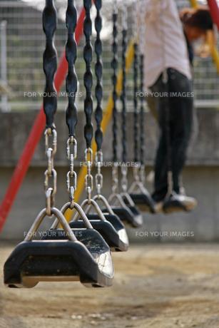 ブランコで遊ぶカップルの写真素材 [FYI01201568]