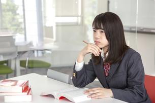 図書室で勉強しながら遠くを見る女子高生の写真素材 [FYI01201618]