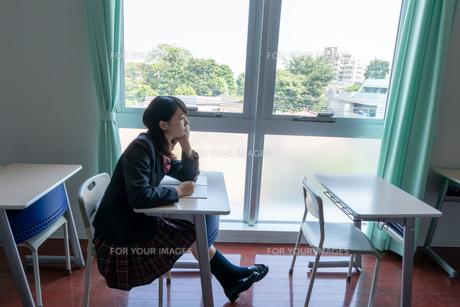 窓際で勉強しながら物思いに耽る女子高校生の写真素材 [FYI01202169]