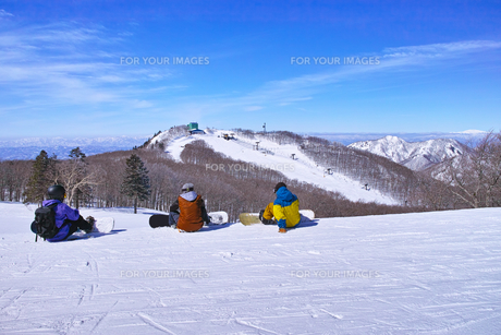 ゲレンデを滑走する前に休憩するスノーボーダーの写真素材 [FYI01202495]