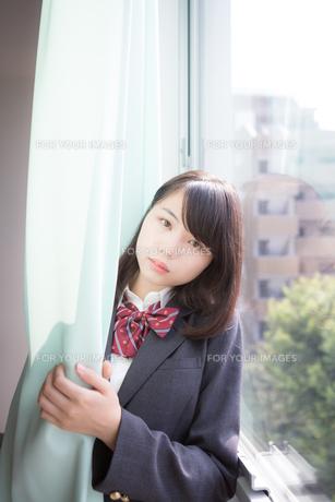 カーテンの中にいる女子高生の写真素材 [FYI01202654]