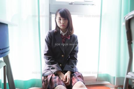 教室の窓にもたれて座っている女子高生の写真素材 [FYI01202664]