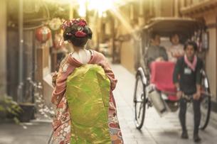 夕方の祇園町の石畳の道に走ってる人力車を背景に赤い着物を着た日本の可愛い芸者の歩いている後ろ姿。の写真素材 [FYI01205181]