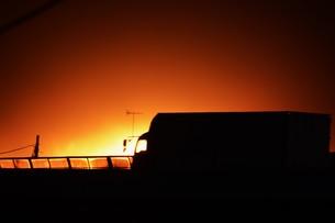 貨物トラックの夕焼けシルエットの写真素材 [FYI01206841]