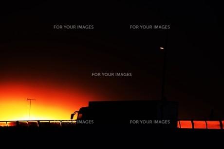 貨物トラックの夕焼けシルエットの写真素材 [FYI01206842]