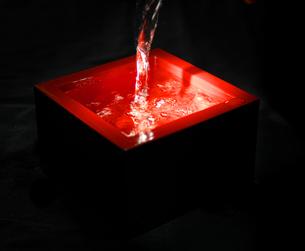 黒バックの朱塗りの酒枡に注がれる日本酒の写真素材 [FYI01207163]