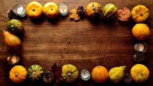 南瓜と枯葉とキャンドルのフレーム 木材背景の写真素材 [FYI01207455]